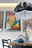 Black and white pendant lamp with inflatable lampshade above dining table in front of row of pictures on wall