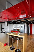 Wooden breakfast bar adjoining stainless steel island counter and bar stools below gallery with red glass balustrade in loft apartment
