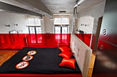 Double bed with black bedspread and red scatter cushions in front of red glass balustrade in bedroom on gallery