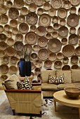 Collection of many wooden bowls on wall behind wicker sofa set with ecru upholstery and geometric scatter cushions