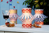 Lantern-style lampshades made from brightly patterned, folded and slit paper on tealight holders