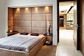 Schlafraum im klassisch strengen Stil mit französischem Bett in gepolsterter Raumnische mit Deckenspots; offene Tür zur Diele