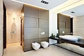 Designerbad mit durchgehender Waschtischplatte an Spiegelwand, WC an holzverkleidetem Saunablock und begehbare Dusche
