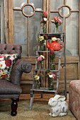 Posies in recycled glass bottles arranged on rustic wooden ladder in vintage ambiance