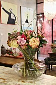Bouquet with willow twigs in glass vase on vintage wooden surface