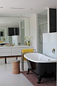 Free-standing bathtub with black, glossy outer wall next to turned wooden stool in modern bathroom