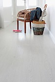 White laminate floor, umbrella in basket with colourful stripes next to armchair