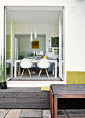View from terrace through open double doors into dining room with classic chairs around modern table