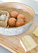 Bowl of onions and garlic next to cheeses on wooden board