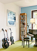 Various musical instruments in front of narrow, tall wooden shelved in corner of room against wall painted pale blue