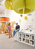 Various pendant lamps with large, slatted, colourful lampshades; woman and man next to desks in workshop