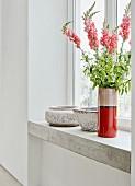 Vase mit Löwenmäulchen auf Beton Fensterbank