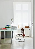 Modern desk and retro chair next to window with white roller blind