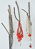 Halsketten aus farbigen Perlen an Ästen aufgehängt