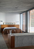 Concrete bathtub and double bed with brown bedspread in bedroom with concrete ceiling