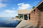 Contemporary house with open wooden louvre doors, encircling terrace and infinity pool with sea view
