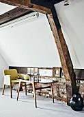 60er Jahre Tisch mit Stuhl vor der Ziegelwand eines Kniestocks in ausgebautem Dach mit den originalen, alten Holzbalken
