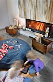 Detail of living room - children playing on floor in front of large, denim beanbag, crate of firewood on castors and fire in fireplace