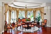 Period furniture in semicircular window bay; chairs with red and gold ornamental pattern in front of lattice windows with swagged curtains in grand interior