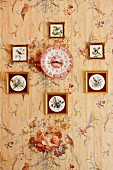 Collection of framed pictures of birds surrounding clock made of red and white wall plate on floral wallpaper
