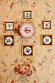Sammlung von gerahmten Vogelbildern an tapezierter Wand mit Blumenmotiv, in der Mitte rotweiss gemusterter Uhr-Wandteller
