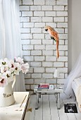 Detail of rustic room; parrot figurine in front of concrete block wall, books on small stool used as bedside table on white board floor