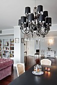 Chandelier with small black lampshades and glass pendants above dining table in open-plan interior with walls painted pale grey