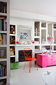 Delicate, orange metal chair next to pink, half-height cabinet in modern interior