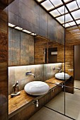 Elegant, contemporary bathroom with countertop basin on wooden counter in niche with antique-brass-effect tiles on wall and indirect lighting