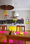 Bold pink and canary yellow accents in open-plan kitchen with dining area, Easter ornaments on dining table below pendant lamps and modern fitted cabinets in background