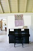 Schwarzes Klavier und Klavierbank, vor Wand mit aufgehängter Stofftasche in folkloristischem Stil