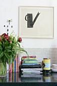 Stacked books on worksurface against tiled splashback below minimalist artwork on wall