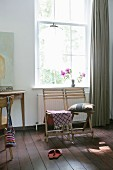 Patterned fabric and cushions on two wooden chairs below lattice window with grey, floor-length curtain to one side