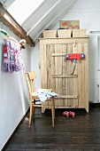 Simple chair in front of wooden wardrobe with storage baskets on top below sloping ceiling