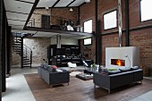 Elegant lounge area and open-plan kitchen in loft apartment with brick and stone walls