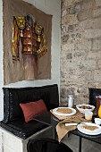 Dining area in corner of vintage room, painting on wall above masonry bench with black seat cushions and set table