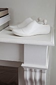 Shoe lasts painted white decorating mantelpiece