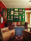 Vintage Ledersessel und antike Ledercouch um Holztruhe als Couchtisch in Wohnzimmerecke, kräftige Farbe an Wand mit Bildersammlung dekoriert