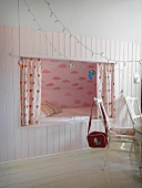 Romantic cubby bed with pink cloud-patterned wall in white wainscoting; rustic ambiance
