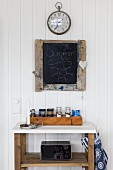 Regal aus Holz mit weisser Ablage, darauf Gewürzflaschen in Kiste, vor weisser Holzwand, aufgehängte Schiefertafel und Bahnhofsuhr