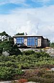 Modernes Sommerhaus aus Holz mit grossen Fensterflächen, am Hang