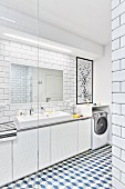 White, modern bathroom with tiled walls & floor, washstand with mirror, strip light & base units and washing machine fitted below shelf