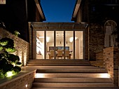 Outside, night-time view of steps leading to single-storey extension between two houses with dining area in illuminated interior