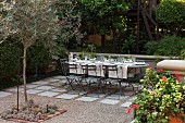 Set table in garden on gravel terrace with stone flags below trees