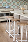 Bar stools with metal frames and wooden seats at breakfast bar in kitchen
