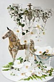 White orchids in a bowl and on a candle holder with glass decorations and an antique miniature horse behind it on a white table