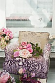 Peonies on armchair with a burnt out pattern cover against a wall hung with a picture
