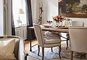 Chairs with beige upholstery at rustic dining table in corner of traditional living room