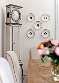 View across table to decorative wall plates next to antique long-case clock