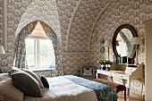 Oval mirror above antique desk with drawers on top and toile-de-jouy wallpaper and curtains in attic bedroom in historical manor house